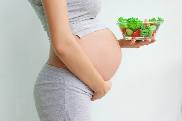 Pancia della donna incinta e insalata di verdure