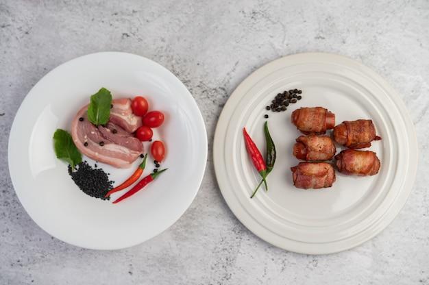 Pancia di maiale avvolta in salsiccia incollata su un piatto su un piatto e pancetta di maiale su un piatto bianco.
