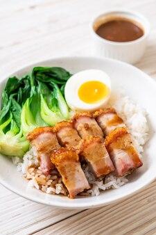 Pancia di maiale croccante su riso sormontato