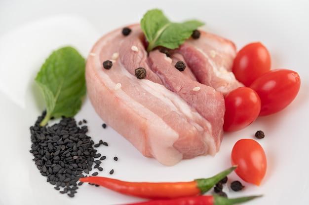 Pancia di maiale in un piatto bianco con semi di pepe pomodori e spezie.