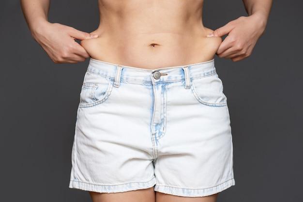 Pancia di una donna con eccesso di grasso su una parete grigia.