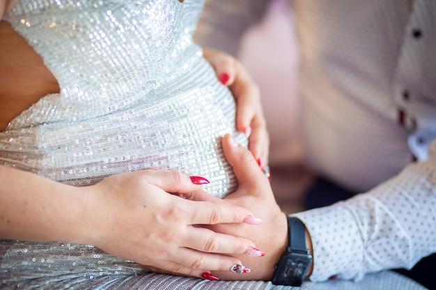 Pancia di una donna incinta in un bellissimo abito lucido primo piano. una ragazza e un ragazzo tengono una pancia incinta