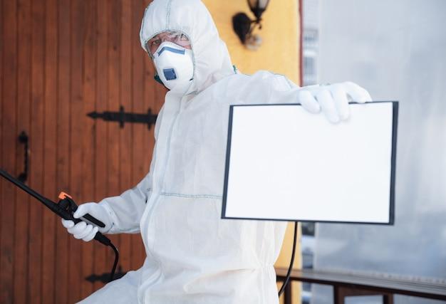 Pandemia di coronavirus. disinfettante in tuta protettiva e maschera spruzza disinfettanti in casa o in ufficio