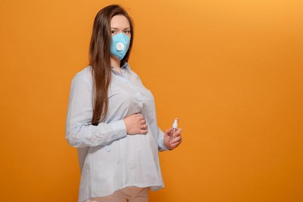Pandemia di coronavirus, giovane donna incinta su sfondo giallo in maschera protettiva medica e spray antisettico in mano