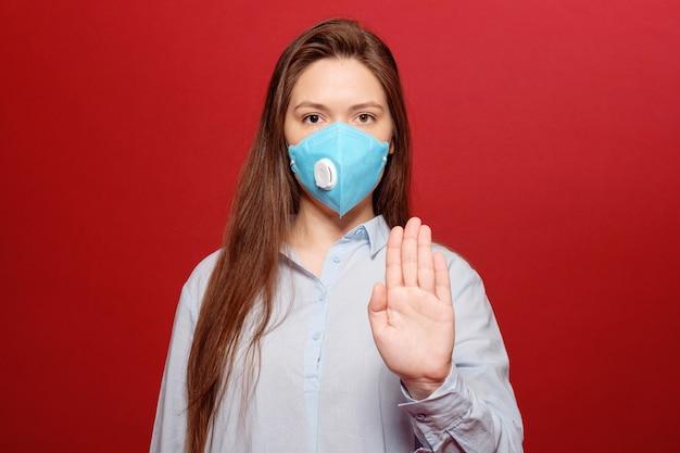 Pandemia di coronavirus, ritratto di close-up di giovane donna su sfondo rosso in maschera protettiva medica,