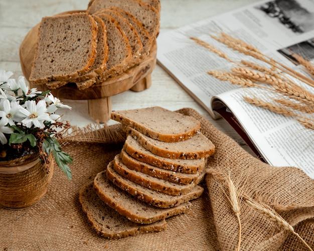 Pane a fette con ramo di grano e fiori