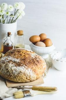 Pane a lievitazione naturale fatto in casa, alcune uova, olio, sesamo, tagliere di legno, coltello di legno e tovagliolo.