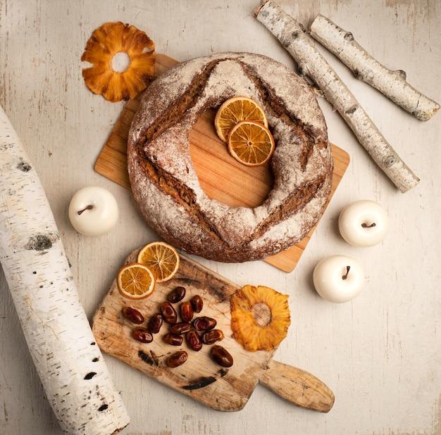 Pane al forno fresco del grano della segale con i frutti secchi su un legno bianco