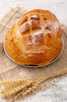 Pane al forno fresco di alta vista sul panno di iuta con grano