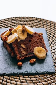 Pane alla banana al cioccolato su una lavagna nera, con banane