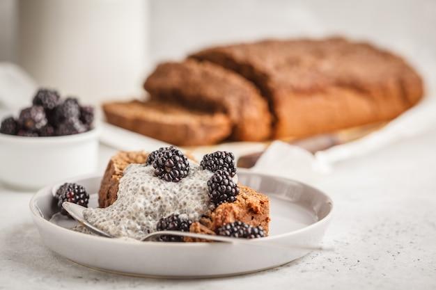 Pane alla banana del vegano del cioccolato con il pudding e le more di chia, fondo bianco.