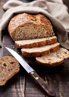 Pane appena sfornato con asciugamano da cucina e coltello sul bordo di legno scuro