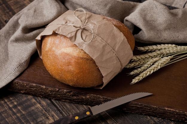 Pane appena sfornato con asciugamano da cucina e coltello sul tagliere di legno