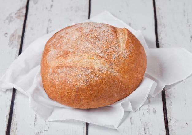 Pane appena sfornato con asciugamano da cucina e grano sul bordo di legno bianco