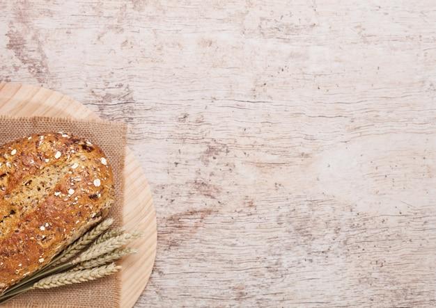 Pane appena sfornato con avena e asciugamano da cucina su sfondo di tavola di legno