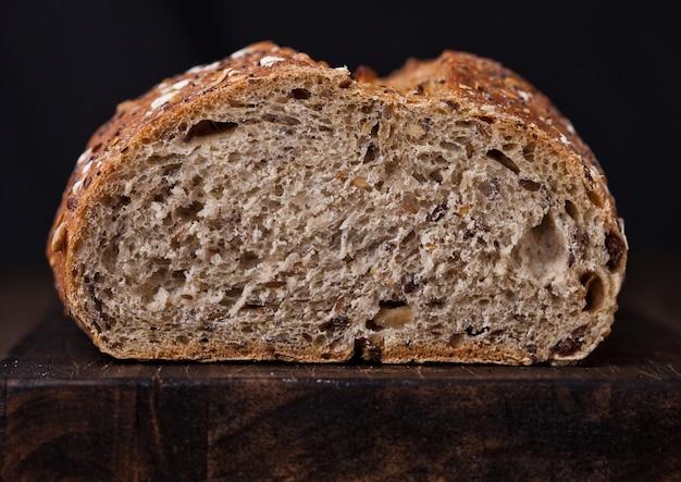 Pane appena sfornato con avena sul fondo del bordo di legno
