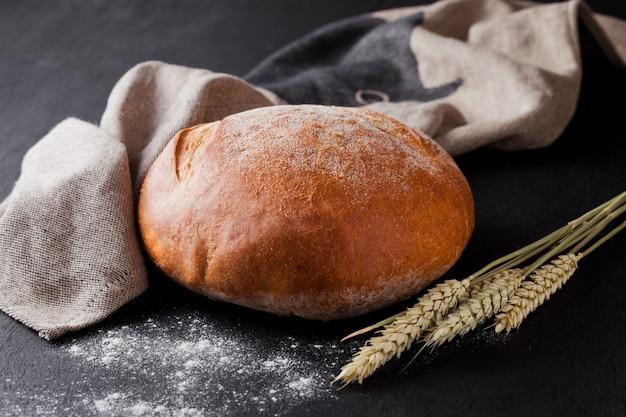 Pane appena sfornato con farina e asciugamano da cucina su sfondo nero