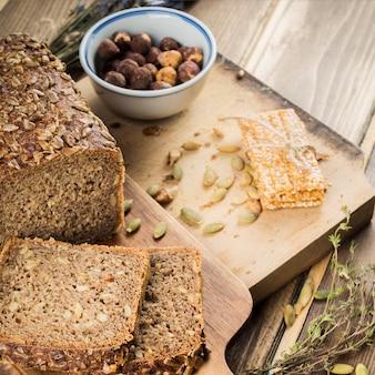 Pane appena sfornato con guarnizione di semi di girasole e barretta proteica sul tagliere