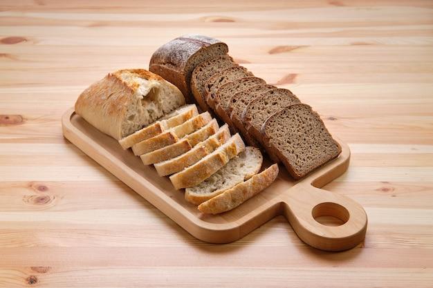 Pane bianco e nero sul tagliere di legno