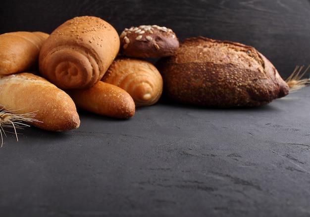 Pane bianco, grigio e di segale, baguette, rotolo con semi di sesamo su sfondo nero