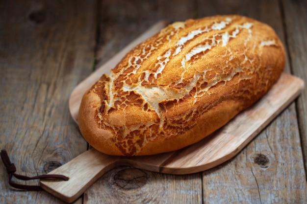 Pane bianco su una tavola di legno. il pane nel forno è appena arrivato dal forno. cottura fresca su un tavolo di legno.