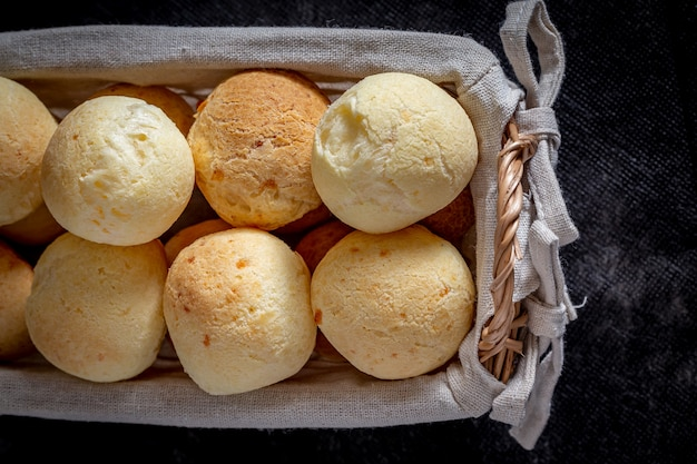 Pane brasiliano al formaggio fatto in casa, aka 'pao de queijo' in un cestino rustico.