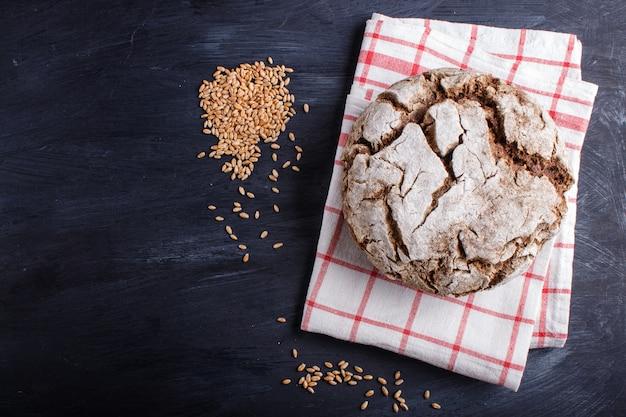 Pane casalingo senza lievito con segale integrale e chicchi di grano su legno nero