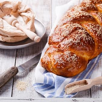 Pane challah con semi di sesamo. pasticceria, farina e semi di sesamo