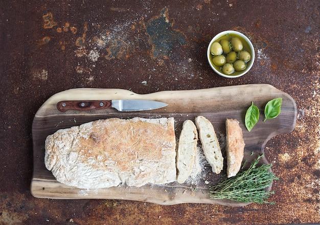 Pane ciabatta fatto in casa appena sfornato con olive, basilico e timo su tavola di legno di noce su metallo arrugginito grunge, vista dall'alto