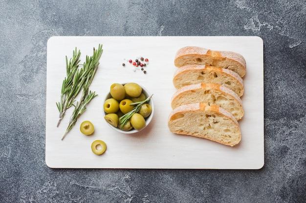 Pane ciabatta italiana con olive e rosmarino su un tagliere