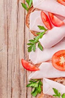 Pane con fette di prosciutto, pomodori freschi e prezzemolo