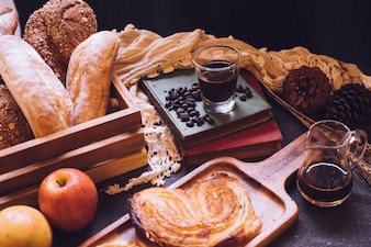 Pane cotto, mele e caffè su un tavolo.