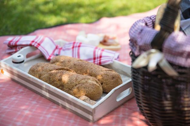 Pane cotto nel vassoio con cesto sul panno
