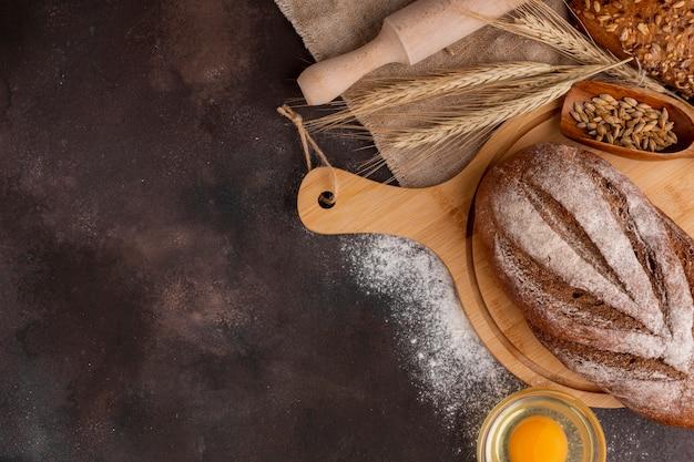 Pane cotto sul bordo di legno e sull'erba del grano