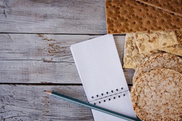 Pane croccante, fiocchi, grano saraceno, biscotti con girasole su uno sfondo a trama