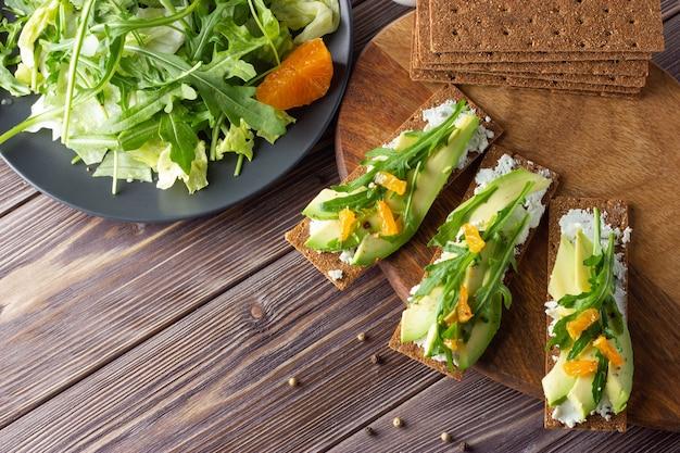 Pane croccante integrale con formaggio, avocado e foglie fresche con insalata su fondo in legno.
