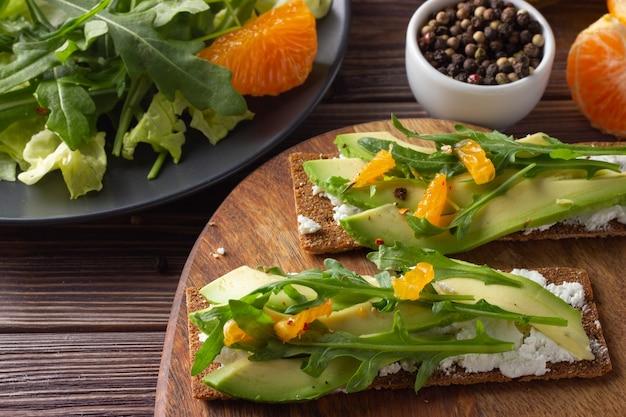 Pane croccante integrale con formaggio, avocado, foglie fresche e mandarino su fondo in legno