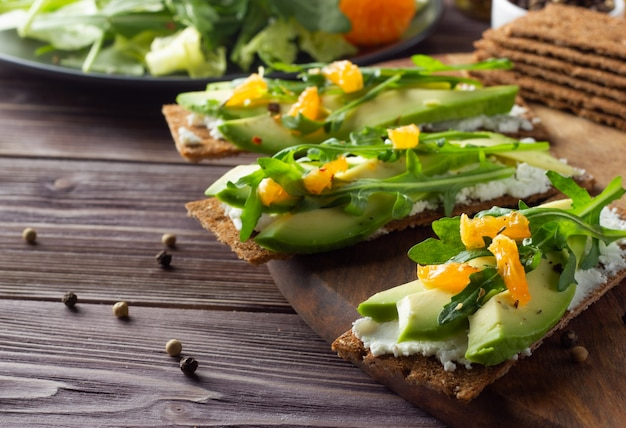 Pane croccante integrale con formaggio, avocado, foglie verdi e mandarino