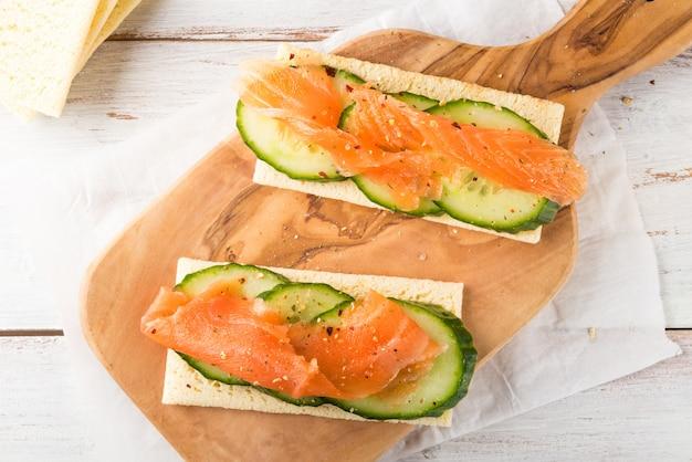 Pane croccante senza glutine, fette di cetriolo e salmone affumicato