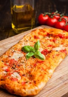Pane della pizza con i pomodori e l'olio d'oliva sul bordo di legno