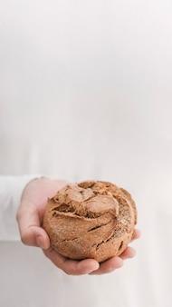 Pane della tenuta della mano con fondo bianco
