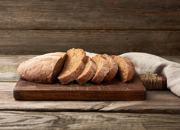 Pane di farina di segale al forno rotondo affettato su un tagliere di legno