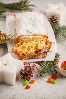 Pane di natale con frutta candita e zucchero a velo in decorazioni natalizie, verticale.