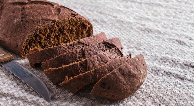 Pane di segale affettato con coltello. pane appena scuro con copia spazio. foto tonica