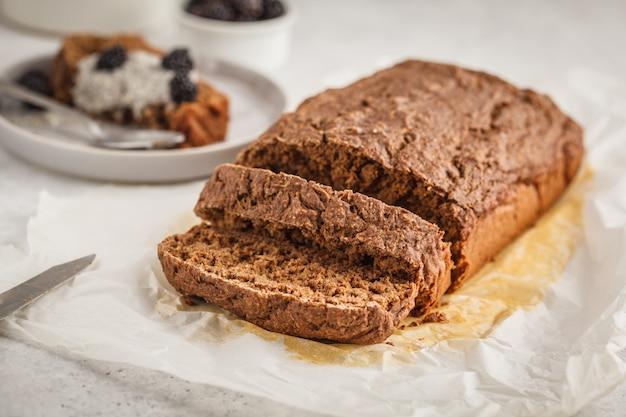 Pane di zucchine vegano al cioccolato con budino di chia e more, sfondo bianco.