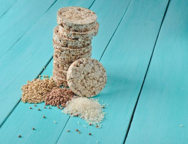 Pane dietetico rotondo rotondo croccante di forma fisica del riso del grano saraceno sulla tavola di legno blu. cibo per dimagrire.