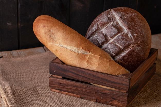 Pane e baguette di segale in un vassoio di legno.