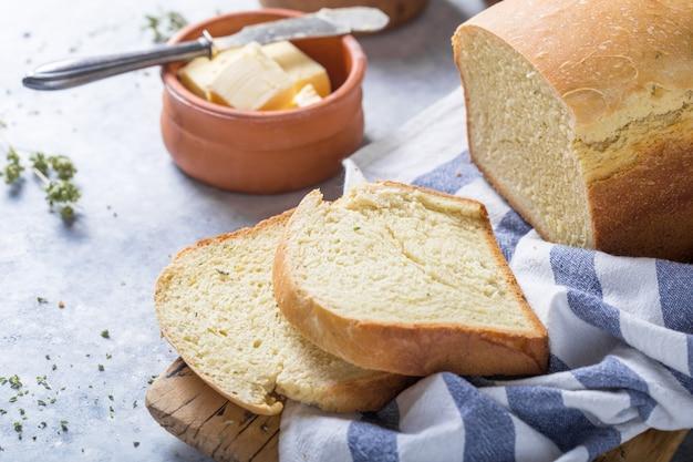 Pane e fette freschi fatti in casa croccanti con olio d'oliva, burro e olive verdi, vista dall'alto. cottura al forno