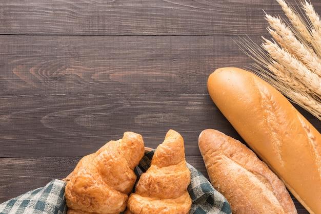 Pane e grano al forno freschi su fondo di legno