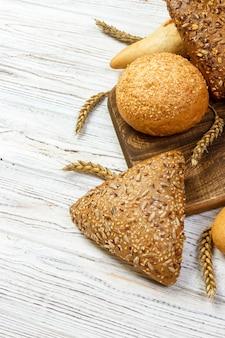 Pane e grano rustici su una vecchia tavola di legno planked dell'annata. f